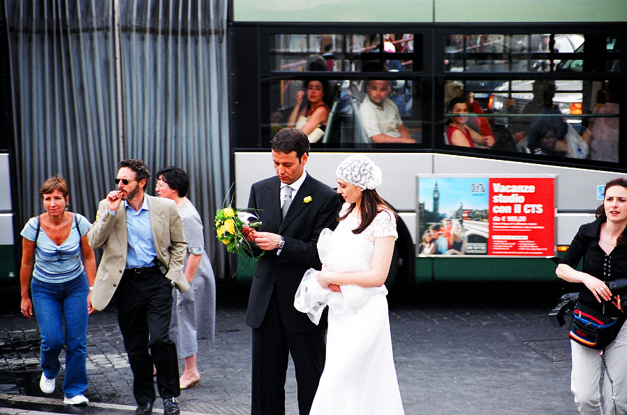 Passengers on a bus catch a glimpse of a groom with his bride moments after their marriage vows.