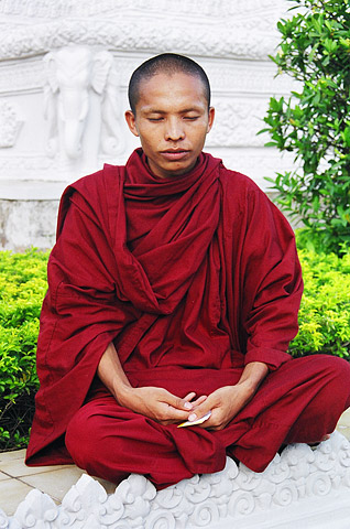 A monk deep in prayer near the Royal Palace.