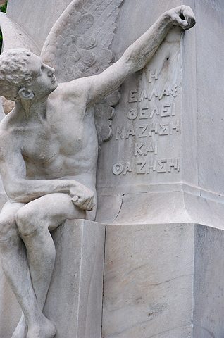 A marble statue outside the former Greek parliament building on Stadiou Street. The inscription reads: {quote}Greece wants to live, and will live.{quote}