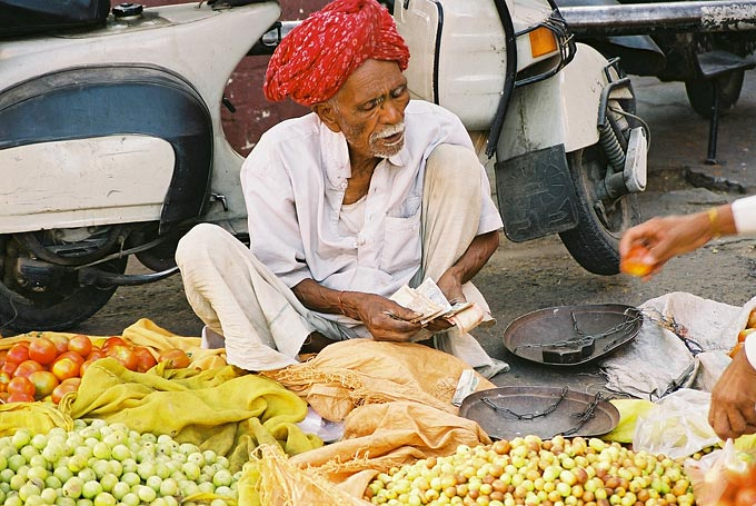 A vendor sells fruit and vegetables near the facade of Hawa Mahal.