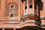 The Hawa Mahal, made of red and pink sandstone, was originally constructed to offer women of the court a vantage point, behind stone-carved screens, to watch the street activities below.