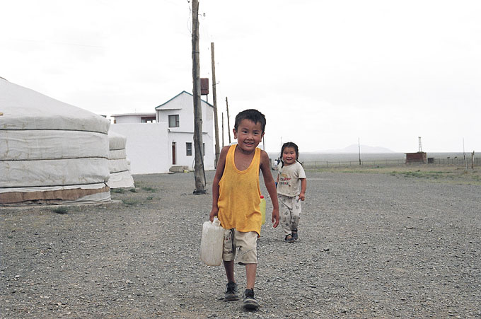 A young boy fetches water for his mother at a ger camp in Omnogov, South Gobi.