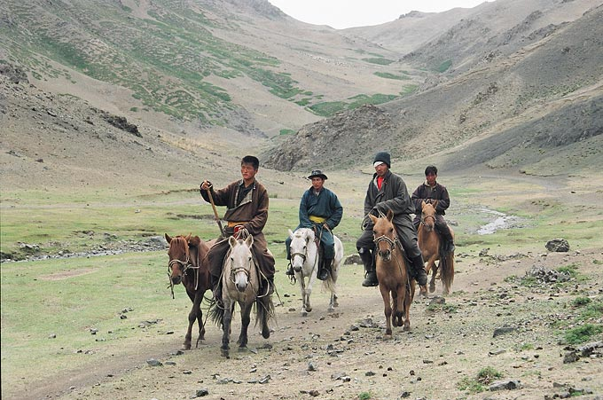 A group of young horse riders suprised by the presence of foreign tourists. Many Mongolians learn to ride horses and camels at an early age.
