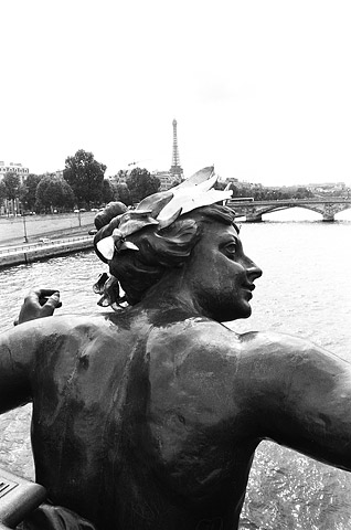 A view of the Eiffel Tower in the distance, taken from Paris's most ornate bridge, Pont Alexandre III.