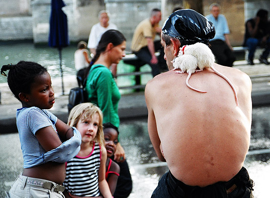 A street artist talks to children during a break in performance at Paris Plage, when part of the Right Bank of the Seine is transformed into an artificial beach during August.