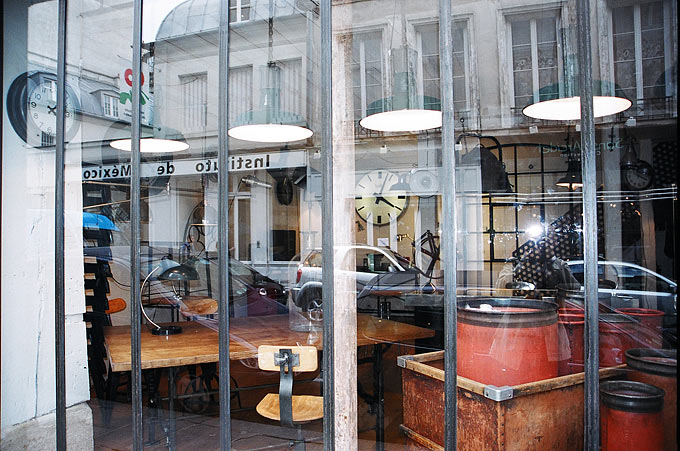 A building is reflected in a shop selling industrial furniture in the historic Marais quarter.