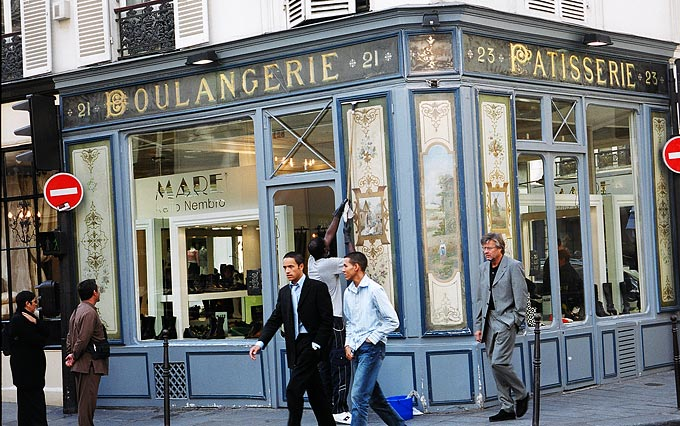 Shoppers stroll past an old patisserie shop now selling shoes in the historic Marais quarter.