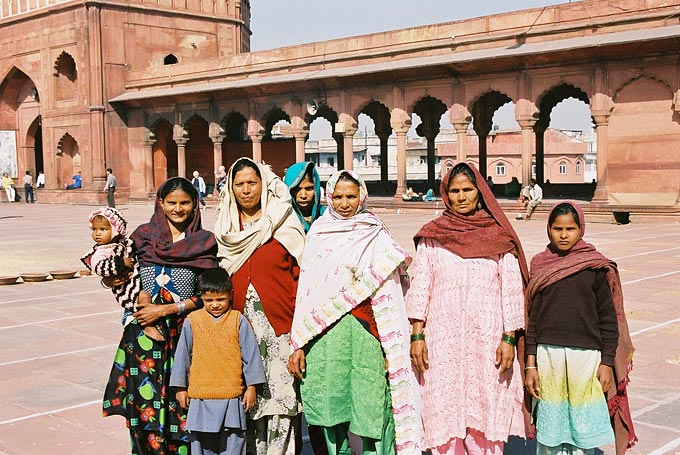 A proud family poses for a foreign tourist inside the grounds of Delhi's Jami Masjid, the Grand Mosque located in the city's Old Quarter.