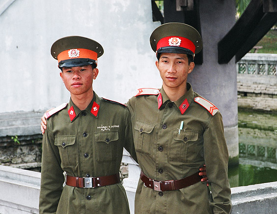 Two soldiers pose for a foreign tourist in the capital Hanoi.