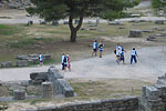 Shot putters and volunteers walk amid the ruins at ancient Olympia, the birthplace of the Olympics.