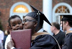 A graduate of Elon's MBA program is greeted by his son after leaving the ceremony.