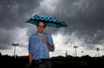Graphic designer Christopher Eyl poses for a portrait as a summer storm rolls in.