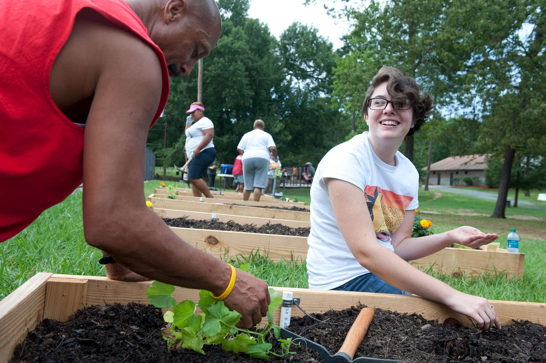 Elon student Lauren Clapp plants a community garden with community volunteers at the Mayo Bigelow Center at North Park in Burlington. Lauren created the garden as part of her research on food justice.