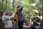 First year students work together to complete Elon University's low-ropes Challenge Course as a group-building exercise.