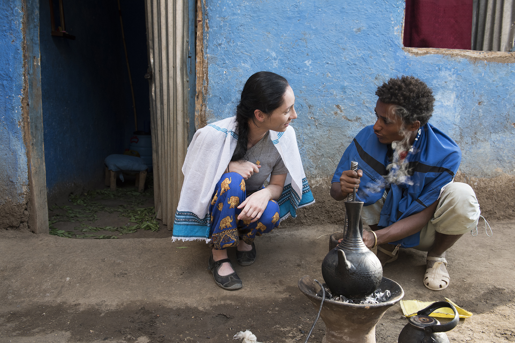 Kat DiBona learns to grind coffee by hand and brew it over coals during a coffee ceremony, a common part of Ethiopian culture, at a traditional home in Lalibela, Ethiopia.