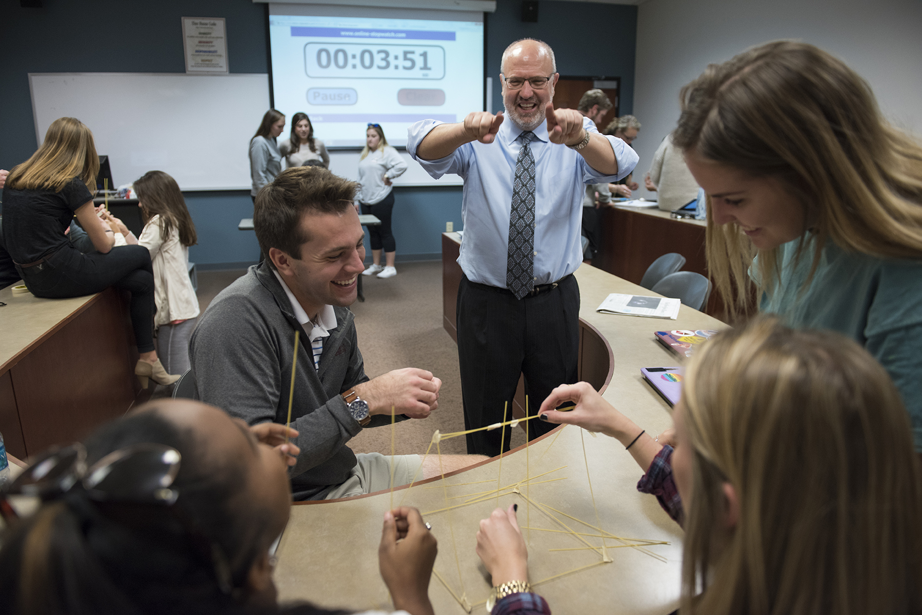Business professor Rob Moorman laughs with his students as they compete to build the largest tower of tape, string, spaghetti and marshmallows.
