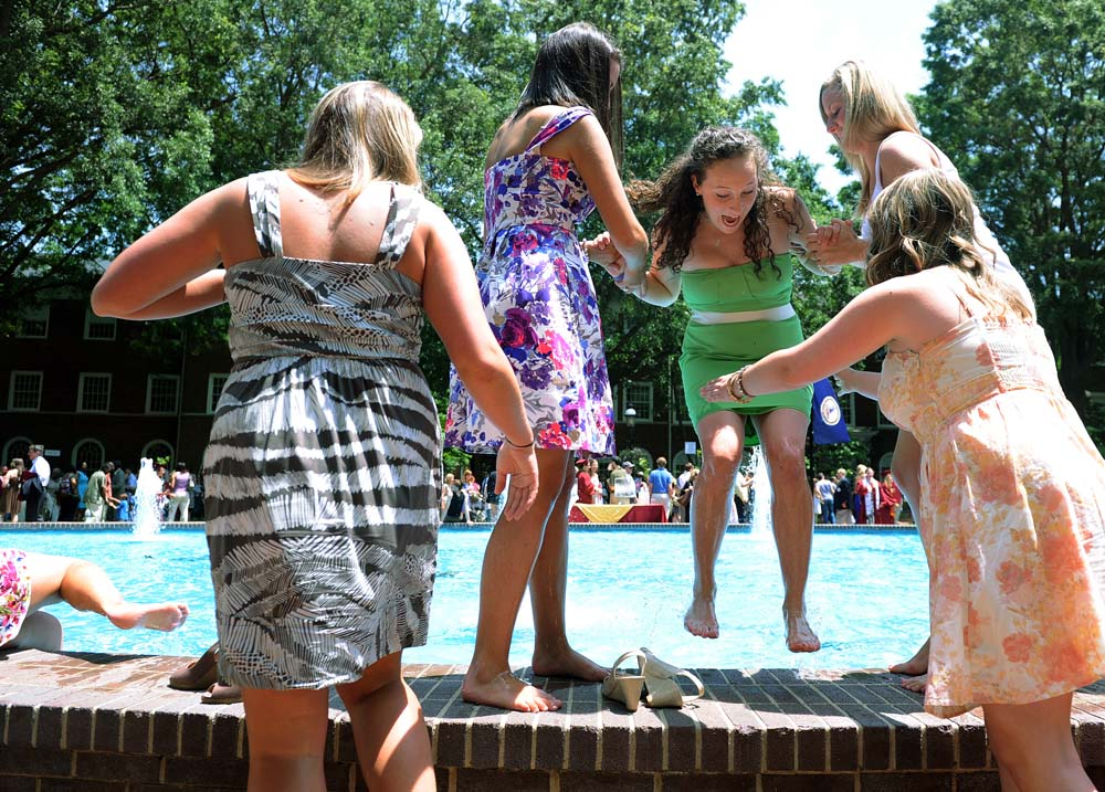 Recent graduates jump in and out of Fonville Fountain, a taboo activity while enrolled at Elon.