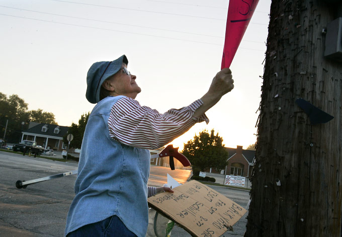 Ann pulls down an outdated yard sale poster on Market Street, Hermann's main drag. A serial yard-saler, Ann knows the confusion old signs cause and does her part to keep things clear.