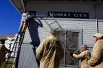 Inmates from Ohio's Hocking Correctional Facility hang newly painted signs on the historic train depot in Murray City, Ohio, a former coal  mining town. The depot was built around the turn of the century and is one of only three original historic train depots left in Ohio.
