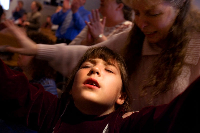 With her mother Terri pressed to her back, 7-year-old Amber Sturgeon's teeth chatter as she raises her arms in worship at River Valley Apostolic Worship Center in Middleport, Ohio. The Apostolic faith, an offshoot of the larger Pentecostal movement, is common within Appalachia. The movement's conservative views reflect the area's political atmosphere.