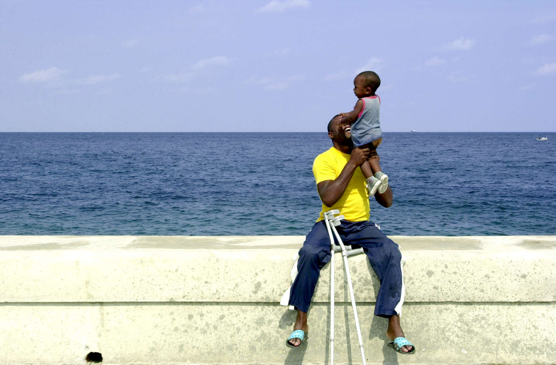 A man and child play together along Havana, Cuba's Malécon, a sea wall that runs along the city's coast.
