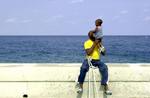 A man and child play together along Havana, Cuba's Malécon, a sea wall that runs along the city's coast.