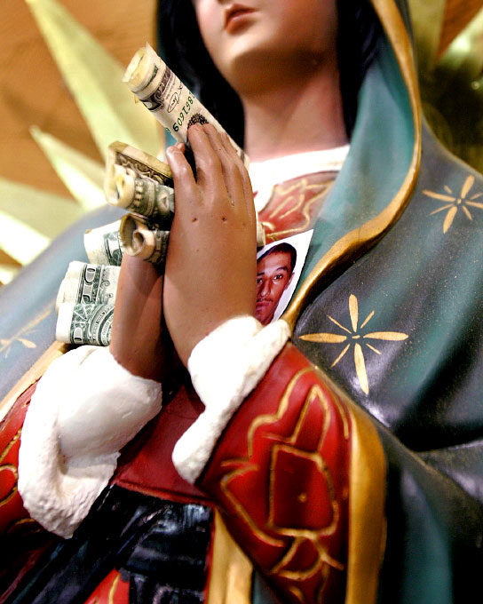 The hands of a Virgin Mary statue overflow with tithes from Mexican workers arriving at the North Carolina Growers Association in Vass, N.C. The men leave their families and homes behind, gambling that the sacrifice will be rewarded with enough money to survive for the year.