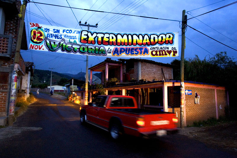 Driving his brother's borrowed truck, Mario Elias Gervacio passes under a banner advertising an upcoming salsa show as he enters his 1,200-population hometown of Tupátaro, Mexico. It's his habit to bow his head and cross himself before cranking the engine.