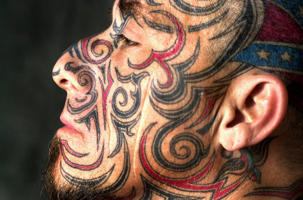 Otto Long poses, showing off his intricate facial and head tattoos, at Little John's Tattoo in Greensboro, N.C.