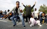 Brittany Davis and Len McCollum (arms raised) dance to the Cha-Cha Slide in an attempt to win free football game tickets before the A&T Homecoming Parade in downtown Greensboro, N.C.