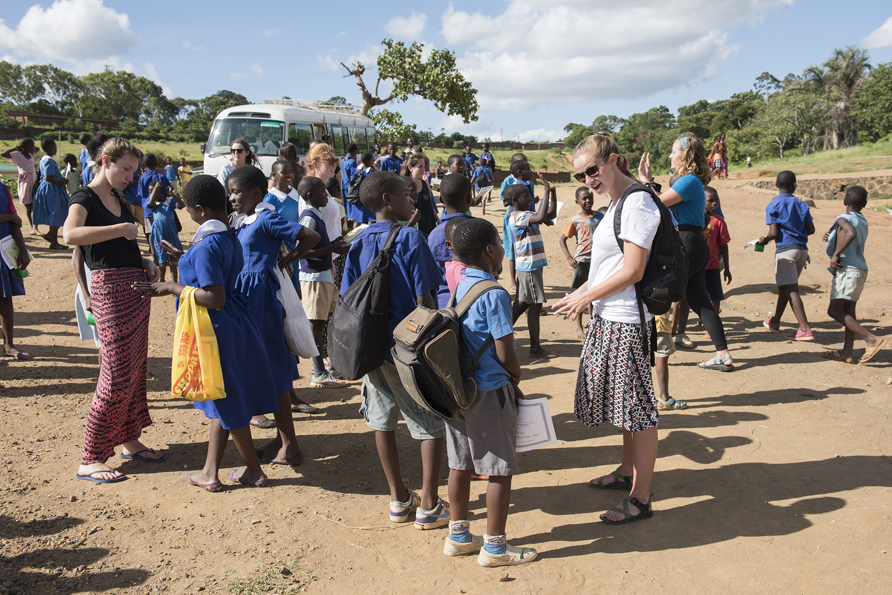 Each day after class, the Malawian children follow the Elon students to their bus, chatting and reaching to hold their hands.