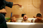 Stefanie Senkiw Krebs pours water over the head of her new son Patrick, 4, while he bathes with his biological brother Joseph, 2, (left) and adoptive brother Peter, 4. Senkiw Krebs and her husband had just returned to their N.Y. home after adopting three brothers from the Ukraine, bringing their family to a total of four adopted children.