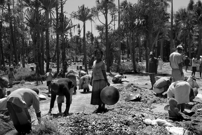 Men, women and children sift for poorer quality stones in a muddy river. Stones are rarely found in the mine itself but are sifted out in several series of washings. The more abundant mines sift very privately with trusted, guarded employees for fear of theft or even the spread of word that a good gem has been found.