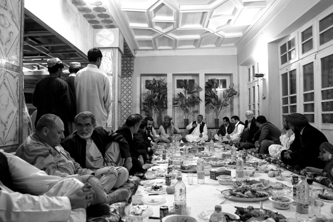 Kandahar officials and Pakistani representatives and businessmen share a dinner on National Pakistan Day in Kandahar, southern Afghanistan. An American officer, left, also attended.