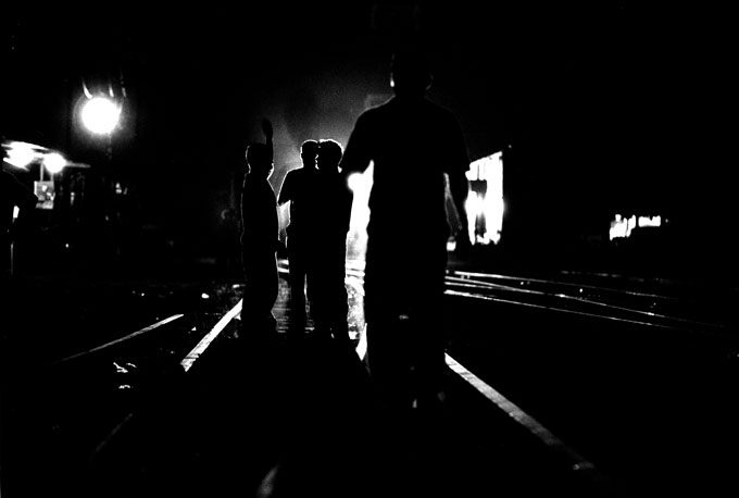 Illegal immigrants discuss ways to jump a freight train under the cover of darkness in Tapachula, Mexico.