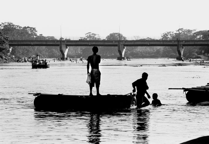 A Honduran man crosses the river between Tecun Uman, Guatemala and Ciudad Hidalgo, Mexico on his way to the U.S.  For 5 pesos per person -- approximately 60 cents --hundreds cross the river illegally. The bridge in the background is a heavily guarded, legal entry point..