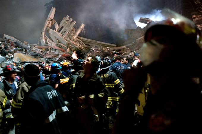 Firefighters pause in the rubble of the south tower when they think they see hands waving from a nearby building. It was just metal reflecting in the lights.