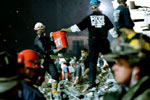 Rescue workers hand buckets of rubble along an assembly line in the night.