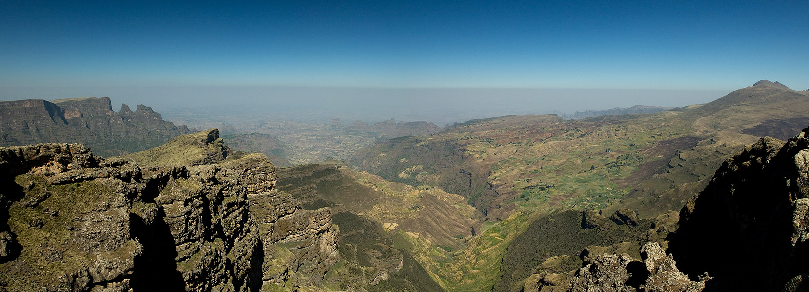 This is a stitched panorama of five images, looking NNW along the escarpment from the viewpoint at Chennek in the Simien Mountains National Park, Ethiopia. The cliffs fall away from this point by over 1000m