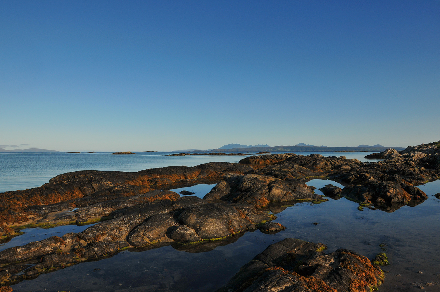 Low tide at Invercaimbe. Early morning light over rock pools, with the Cuilin Ridge on the Isle of Ske beyond.