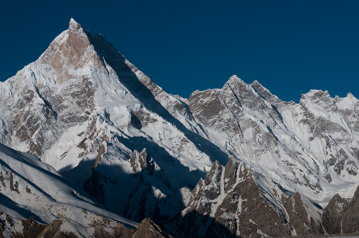 Morning light, from Shokspong on the Baltoro glacier. This is the NW face. The mountain has only ever had four ascents, and none from this side. The first ascent was from the SE in 1960, by Willi Unsoeld, George Bell, Nicholas Clinch and Jawed Akhter. In 1981 a Polish team climbed the lower SW summit, also from the SE and were lucky to get off the mountain alive. The main summit did not get a second ascent until 1983 when a Japanese expedition climbed the same route as the Americans in 1960. In 1985 another Japanese expedition put ten members on the summit via the N ridge, followed the very next day by an Austrian team who had made the first ascent of the NW face. It is now 34 years since anyone stood on the summit.