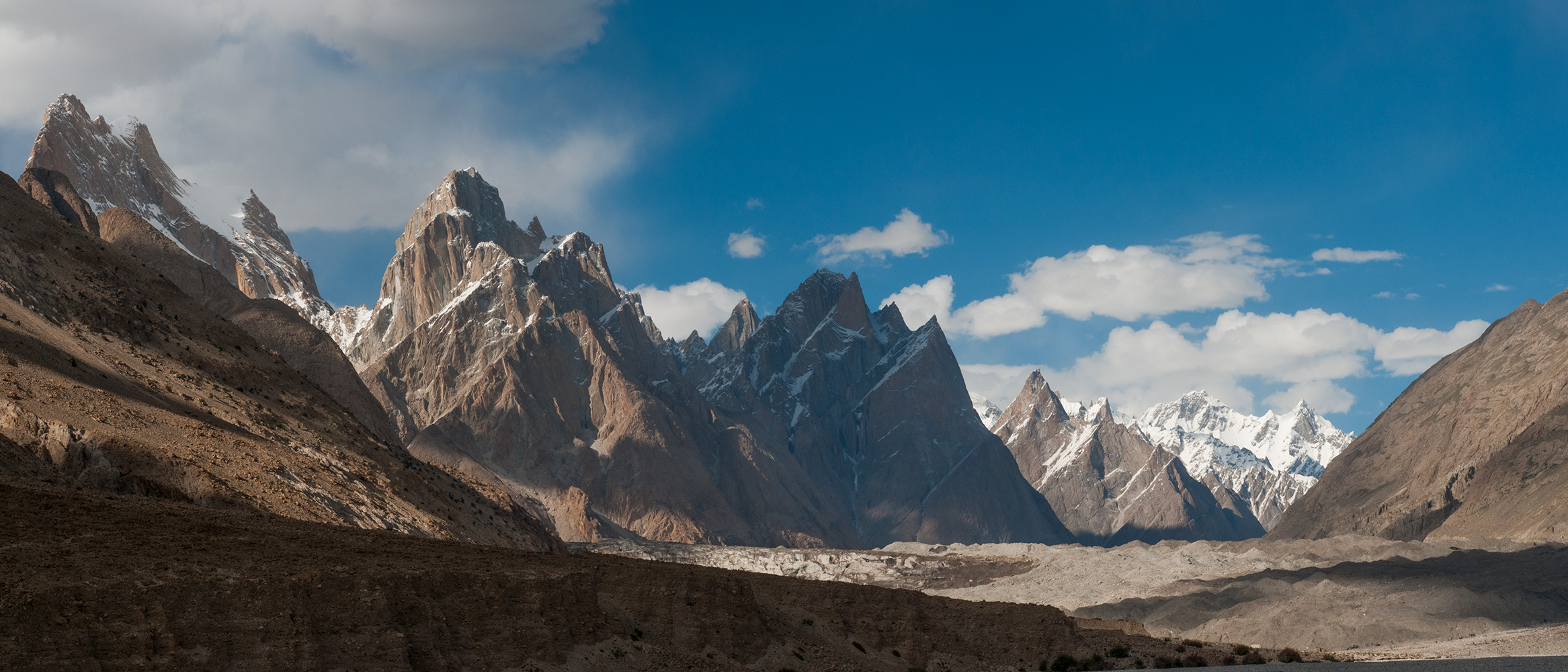 A stitched panorama of two images, taken from the valley floor below Paiju camp. Looking up valley to the Trango Towers, Cathedral Spires and the snout of the Baltoro glacier