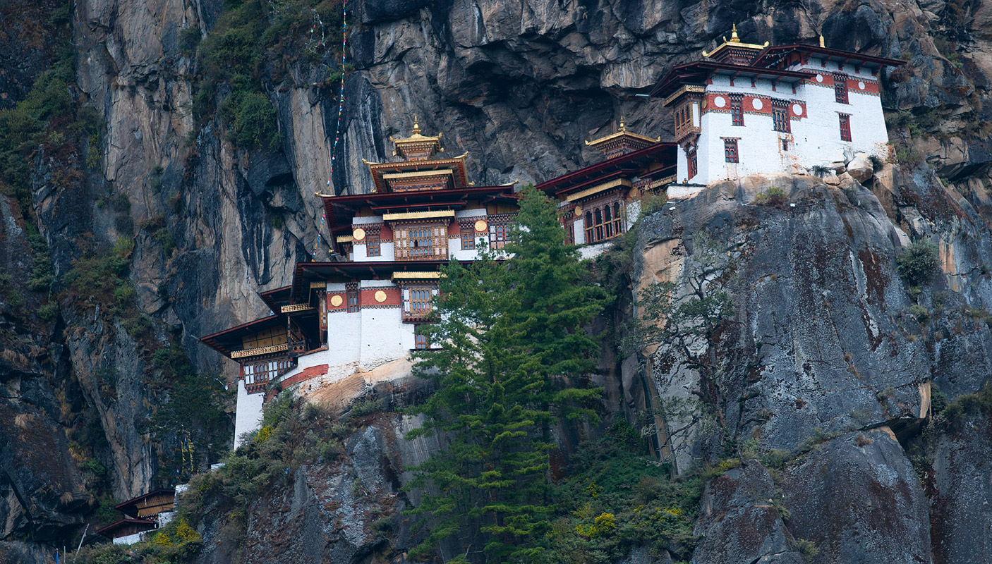 Paro Taktsang (Taktsang Palphug Monastery - also known as The Tiger's Nest) is a a prominent Himalayan Buddhist sacred site and temple complex, located on a cliffside of the upper Paro valley, in Bhutan. A temple complex was first built here in 1692, around the cave where Guru Padmasambhava is said to have meditated in the 8th century. Padmasambhava is credited with introducing Buddhism to Bhutan and is the tutelary deity of the country. Today, Paro Taktsang is the best known of the thirteen taktsang or {quote}tiger lair{quote} caves in which he meditated. Takstang has become the cultural icon of Bhutan. Nikon FM2, 50mm, Fuji Velvia