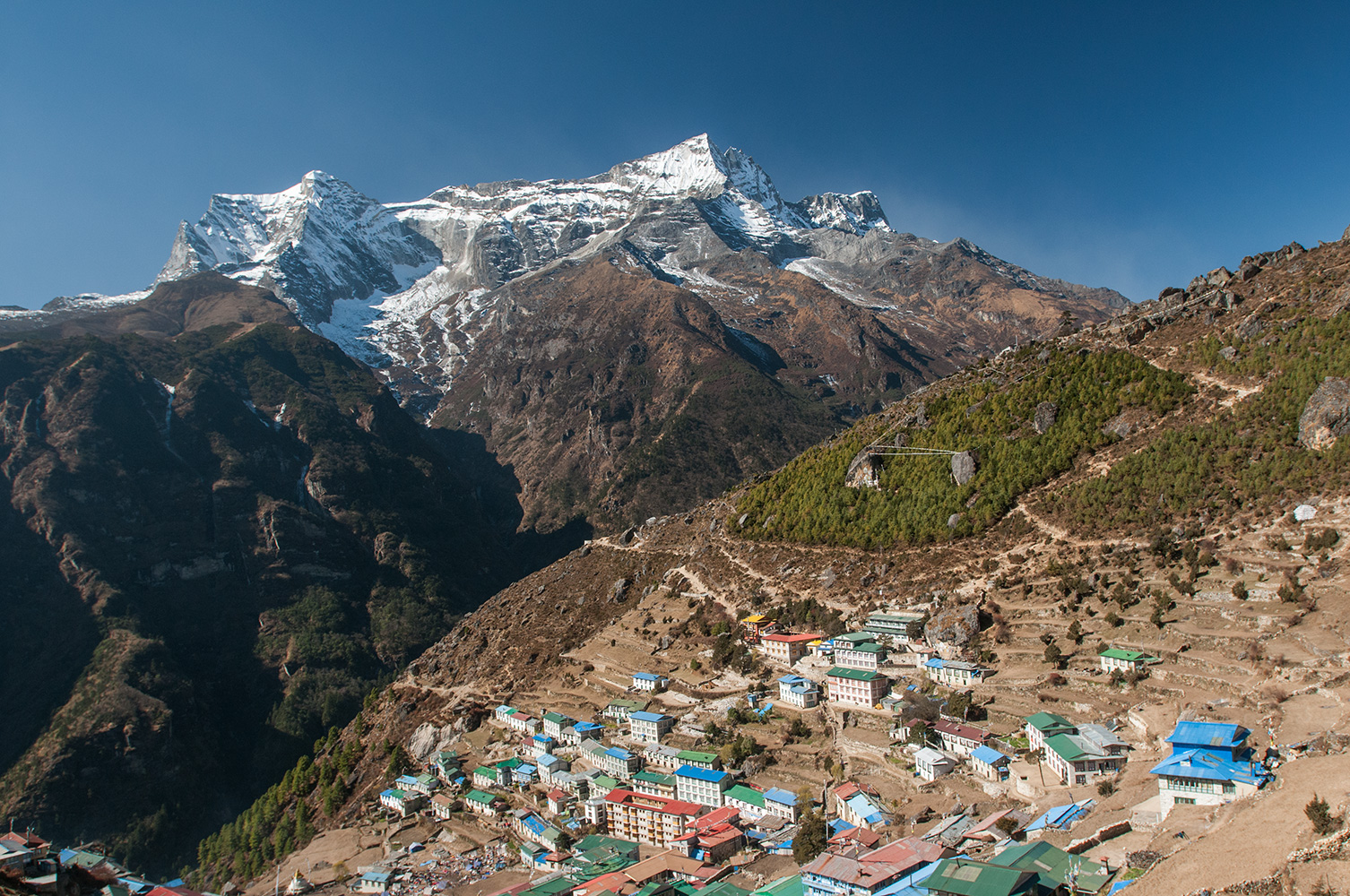 The capital and administrative centre of the Khumbu, Namche is at an altitude of 3440m. The peak in the background is Kongde Ri (6187m). The townhas grown rapidly in recent years as the burgeoning trekking industry bring ever increasing numbers of toursists to the area. Many visitors spend two or tree nights here to acclimatise to the altitude pefore proceeding up valley.Nikon D300, 17-35mm