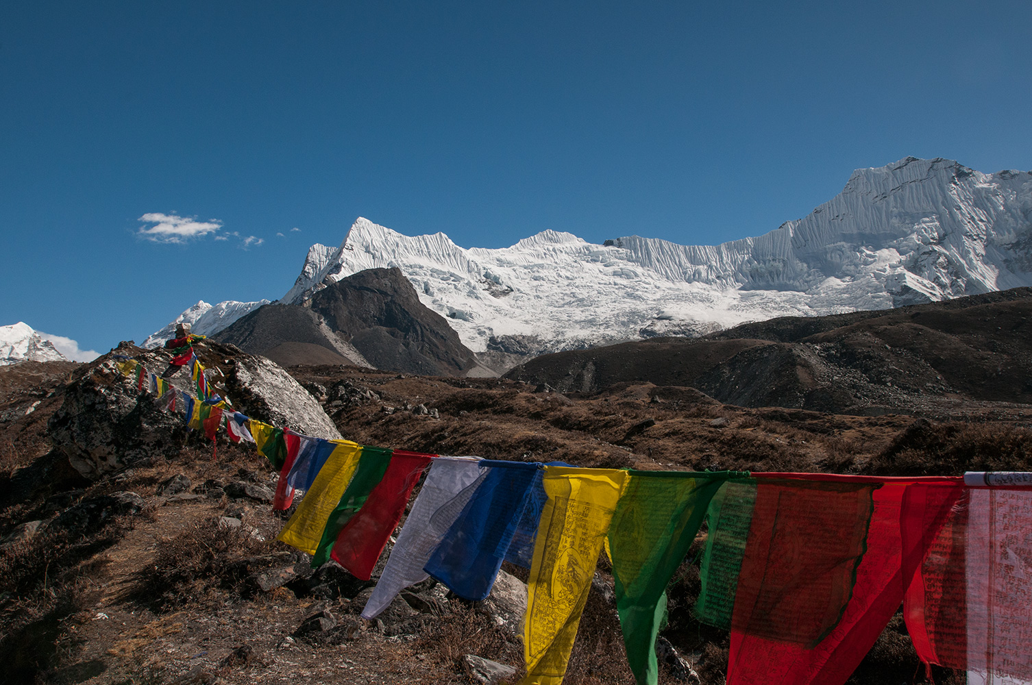 Taken from the trail to Island Peak base camp, the long snowy ridge here is between Amphulapche (left of centre) and Ombigalchen (right). In the distance to the left is Baruntse.Nikon D300, 17-35mm. November 2008