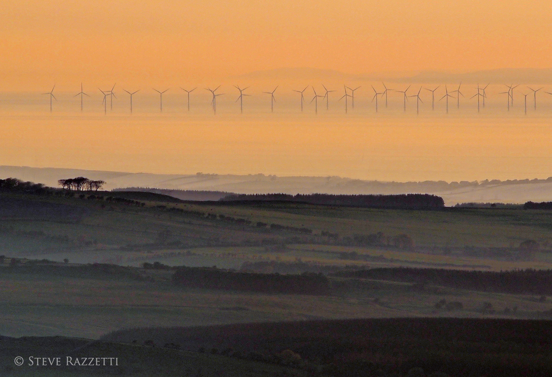 A telephoto at sunset from the top of Binsey. This windfarm was commissioned in 2010 by E.ON and consists of 60 3Mw turbines, is functional for 98% of the year and provides sufficient power for 117,000 households.Nikon D610, 180mm