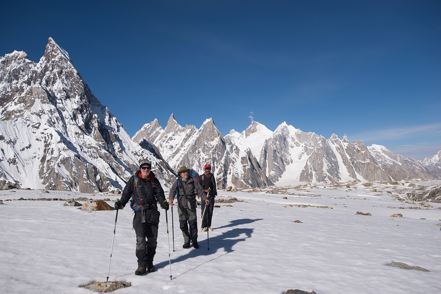 Trekking towards Broad Peak base camp with Mitre Peak (6010m) and Biarchedi (6781m) etc beyond. In this picture are Jim Hartill, Sandy Masson and Zulfikar