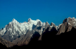 Afternoon light brings out the complex relief of the vertical wall of rock-towers that flank the northern side of the Baltoro. In the distance, a snow covered Paiyu Peak (6610m) provides a background for the Uli Biaho, Trango, Lobsang and Cathedral spires.Nikon F5, 180mm