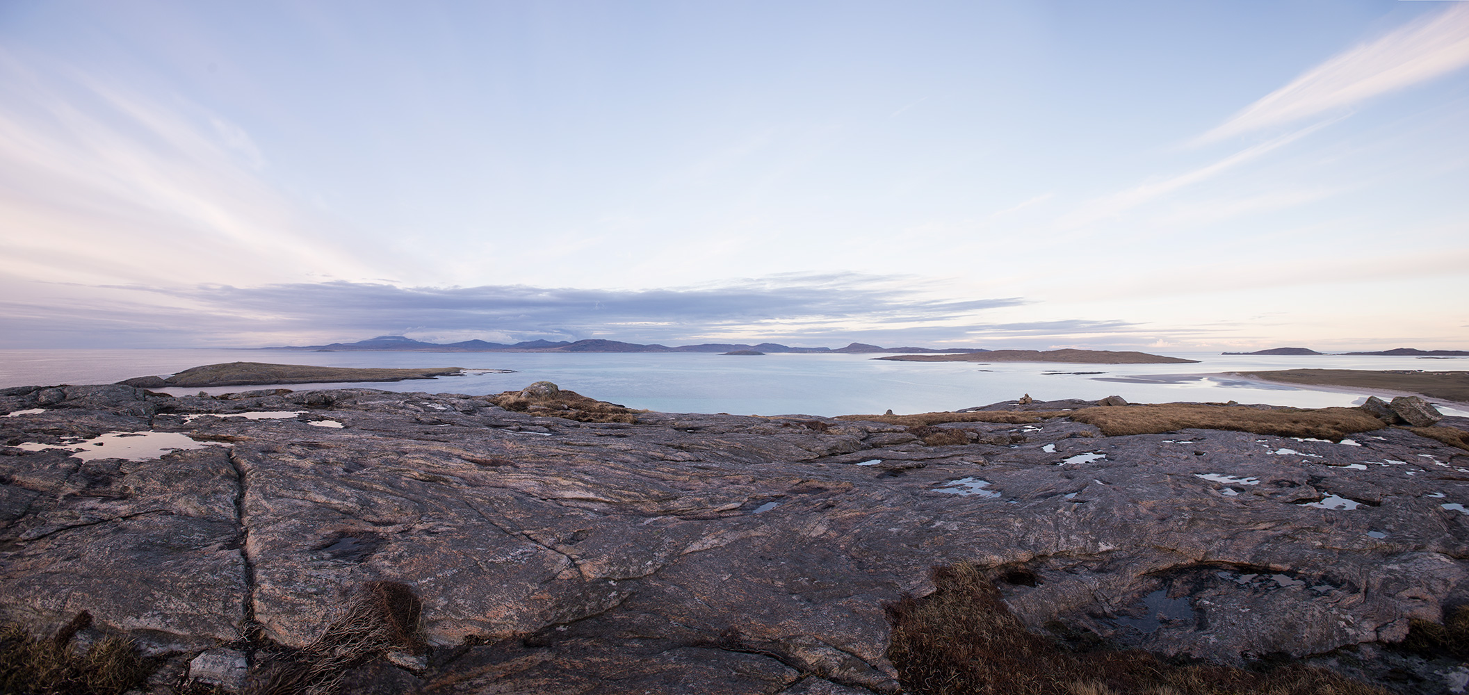 A panorama of four images, looking north over the Sound of Barra to Eriskay and Uist from Beinn Sgurabhal