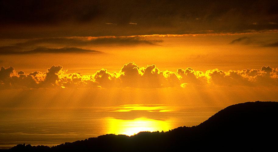 The sun dips towards the horizon behind a bank of cloud - taken from near Hopa, Eastern AnatoliaNikon F5, 180mm, Fuji Velvia 100
